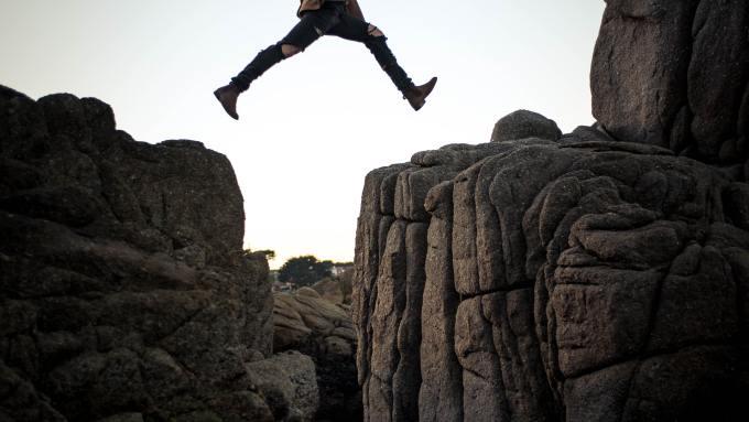 Frau springt über Felsspalt